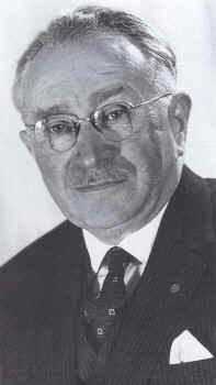 A imagem em preto-e-branco mostra um senhor com bigode usando óculos e paletó com um lenço no bolso externo