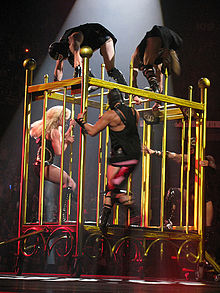 Image of a blond female performer inside a giant golden cage. She is being chased by three men dressed in black S&M outfits.