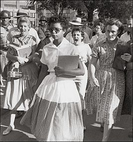 Elizabeth Ekford tries to go to Little Rock School on September 4, 1957. In the background is a screaming crowd of white people and soldiers of the National Guard.