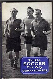 "A black and white image of three men, one much younger than the other two, jogging while wearing shirts and shorts. In the bottom right hand corner is a blue square upon which is printed ""Tackle Soccer This Way - Duncan Edwards"""