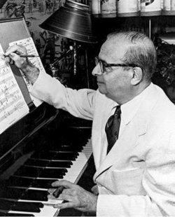 Greyscale photograph of Max Steiner with a piano
