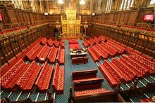 Wood panelled room with high ceiling containing comfortable red padded benches and large gold throne.