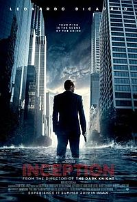 A man in a suit with is back turned and a gun in his right hand, against a cityscape with water coming up to his knees.
