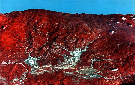 พื้นที่ภัยพิบัติโคลนถล่มตำบลพิปูนประมาณ พ.ศ. 2532  สีขาวบนเขาคือพื้นที่ที่โคลนถล่ม สีขาวบนพื้นราบคือพื้นที่ตั้งถิ่นฐานเดิมของชาวบ้าน โปรดสังเกตทางน้ำออกที่ลูกศรชี้