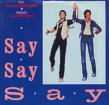 "Against a blue background, ""Say Say Say"" is printed in pink and takes up the left and bottom of the image. To the right, there is an artwork depiction of two men holding each others' hands in the air."