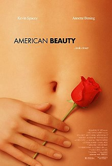 "A young woman's bare belly. Her right hand holds a rose by its stem against her skin, tipped 30° to the right. ""American Beauty"" appears in black letters above her navel, with ""... look closer"" below and to the right in smaller print."