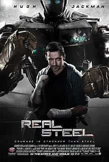 Hugh Jackman in character in a boxing pose in front of a large boxing robot in a similar pose.
