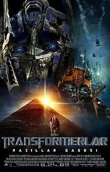 The faces of two robots stand atop a pyramid. A helicopter flies over an industrial facility on the right side of the image, and a young couple is seen in front of the pyramid. The film title and credits are on the bottom of the poster.