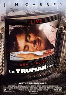 "Film poster. On the side of the building is a large screen, showing a man laying his head on a pillow, eyes closed and smiling. Digital text above and below the screen state ""LIVE"" and ""DAY 10,909"", with the film's title right below it. Text at the top of the image includes the sole starring credit and text at the bottom includes the film's tagline and credits."