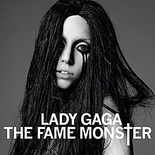 "A brunette, whose black hair falls all around her face and covers her torso and right eye. Black eyeliner runs down her face in two streaks from her left eye. In front of her, the words ""Lady Gaga"" and ""The Fame Monster"" are written in white capital font, with the T of Monster being stylized as a cross (†)."