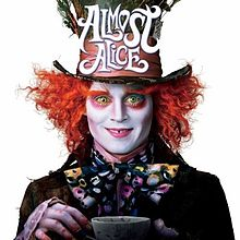 The mad hatter staring directly at the viewer holding up a cup of tea.