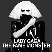 "A woman in a blonde blunt bob cut. She wears a shiny black leather dress covering her body completely. With her right hand she holds the collar of the dress and uses it to cover her mouth. In front of her, the words ""Lady Gaga"" and ""The Fame Monster"" are written in white capital font, with the T of Monster being stylized as a cross (†)."