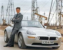 Bond in a grey suit, leaning against a roadster with oil rigs in the background.