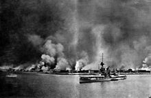A city burns in flames; in the foreground, a large battleship sits in the water. A smaller vessel is berthed next to her. Another small ship sails away from the city on the left.