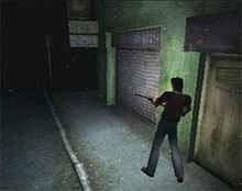 A video game screenshot that is a digital representation of a dark town street. A man with his back to the viewer holds a rifle as he walks along the side of a green building.