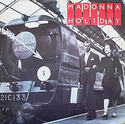 "The black and white picture of the engine of a train. A symbol of a white arrow is present at the center of the engine's front. The words ""Golden Arrow"" is written on the arrow. A couple walks beside the engine on the platform, the man carrying a suitcase. On the top right corner of the image, the words ""Madonna"" and ""Holiday"" are written in white, on bright red stripes."