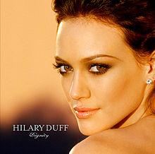 """Gương mặt và đôi vai của cô gái đang nhìn về phía vai trái của cô. Cô có một mái tóc màu nâu và đang đeo một đôi khuyên tai pha lê nhỏ. Ở bên trái của hình, chữ """"Hilary Duff"""" được viết trong màu bạc, in hoa, cùng tên """"Dignity"""" cũng trong màu bạc, in nghiêng trong nét chữ mềm mại, nằm dưới chữ còn lại."""