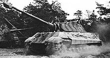 A large tank throws dust from its tracks as it drives by, a man is casually sitting on the front of the turret.