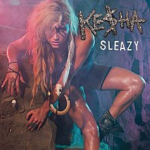"A blond-haired woman rests on a rock wall. She wears tribal clothes: a dark suit, boots and bone ornaments. She has three strips painted across her left eye and a skull, and a long white strip, throughout her left arm. Over her left shoulder the words ""Ke$ha"" and ""Sleazy"" are written."