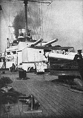 Two large gun turrets on a warship. Thick black smoke billows from the funnels.