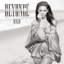 "Grayscale portrait of a woman who is standing next to a beach. She is wearing a metallic short dress. She crosses her left arm across her body while the other arm rests against her face. Next to her image, appear the words ""Beyoncé"" and ""Halo"" in silver capital letters."