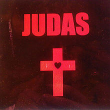 """Judas"" is written in capital red letters on a black background. Below is a red cross with a black heart in the middle."