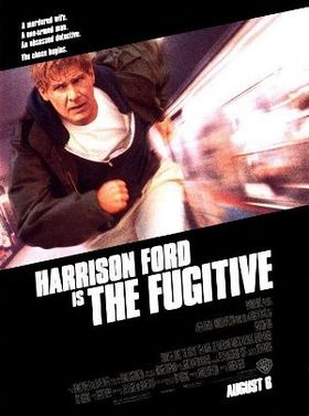 "A black poster. Above in bold white letters are the lines: ""A murdered wife."" ""A one-armed man."" ""An obsessed detective."" ""The chase begins."" In the middle is a picture of an older male with brown hair wearing a white t-shirt, black zippered jacket, black coat, and white pants; running parallel to a train on a subway platform. Below in large white typeface is the line: ""Harrison Ford"". Below that in smaller white typeface reads the line: ""is"" with a larger white typeface next to it reading: ""The Fugitive"". The film credits appear underneath it in a small grey typface, along with a line that reads: ""August 6"" in a larger white typeface."