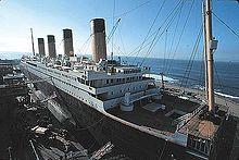 Một con tàu giống với Titanic đang được xây dựng tại một cảng, với nền trời xanh và sóng nhẹ.
