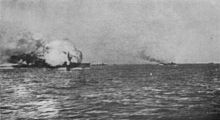 A ball of flame engulfs a large gray warship. Several smaller ships are seen in the distance.