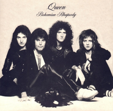 "The four members of the band sit together in front of a sandy-coloured background wearing predominantly black clothing. Mercury appears to be the dominant figure, sat in front of the other three members. From left to right, John Deacon, Mercury, Brian May, Roger Taylor. All four individuals are looking directly at the camera with a neutral expression on their face. Above the band is some black text, printed in an elegant, italic font face. The word ""Queen"" followed by ""Bohemian Rhapsody"", the latter of which is positioned under the band name in the same format yet smaller font."