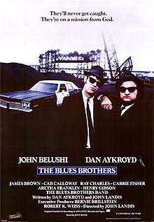 "Movie poster with two of the main characters on the right-side of the image. They are both wearing black suits, hats, and sunglasses and facing forwards. The man on the right is resting his arm on the shoulder of the man on the left. A police car is present on the left side of the image behind them. At the top of the image is the tagline ""They'll never get caught. They're on a mission from God."" At the bottom of the poster is the title of the film, cast names, and production credits."
