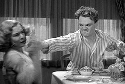 Cagney, in stripped pajamas, looks angry as he reaches across a breakfast table with the grapefruit in his hand.
