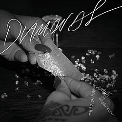 A black-and-white picture of hands rolling diamonds in a cannabis paper. The word 'Diamonds' is written in white letters across the picture, while an 'R' logo is present in the right corner.