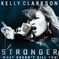 "A blue-tint-in-a-black-and-white image of a woman singing. Her right hand is holding a vintage carbon microphone in front of her mouth. The microphone's wire is resting on her left hand between her thumb and her index finger. Below her, the words ""Stronger"" and ""(What Doesn't Kill You)"" are written in white upper-case letters."
