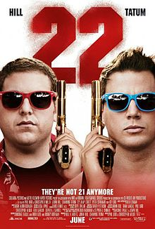 The faces of two men wearing colorful sunglasses, and holding guns up beside their faces. Above them the number '22' in red.