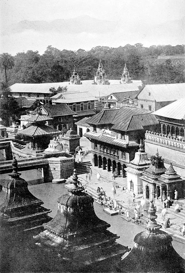 Black and white photograph, from a raised viewpoint, of a river lined by buildings.  The bank of the river is paved with steps to the water itself.  A foot bridge crosses the river at the left of the image.  People are gathered below at the river bank.  In the background, trees can be seen behind rooftops.
