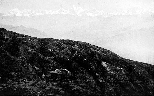 Black and white photograph of a mountain range.  Half of the image is filled by the side of a mountain in the foreground, slanting down to the right.  In the background, further faint mountain slopes can be seen.  At the very top of these, at the furthest distance, are white, snow topped mountain peaks.