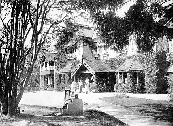 Black and white photograph of a large two storey house in the country. Four women stand in the background, by the front door.  A girl sits on steps in the foreground, in the shade of a tree.